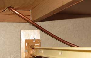 The copper tubing leads into a drawer space under the refrigerator