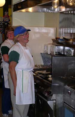Gwen is behind Claudia, the cook, standing at the grill.