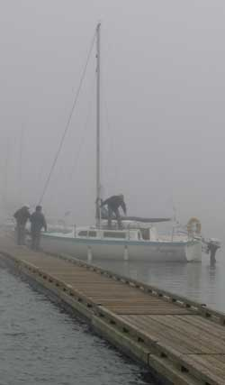 A noon-time fog rolls in causing navigation problems. The mast of the next sailboat is only 40 feet from this boat but can barely be seen in the fog.